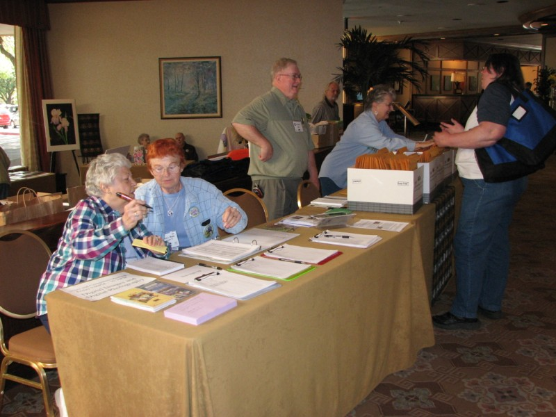Co-Chair Pat Byrne consults with Patsy Rosen, and Jim Landers chats while Margaret Ann Smith looks for a registration packet
