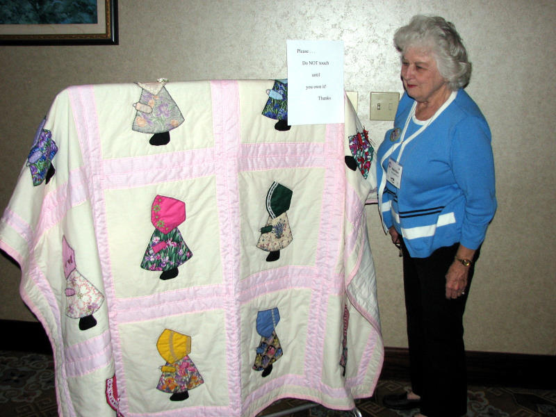 Nelda Moore admires Kitty Lack's  bonnet girl quilt donated for the raffle
