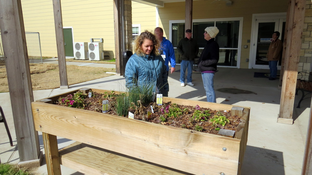 BIS President Karen Woods inspects a flower box in the courtyard.