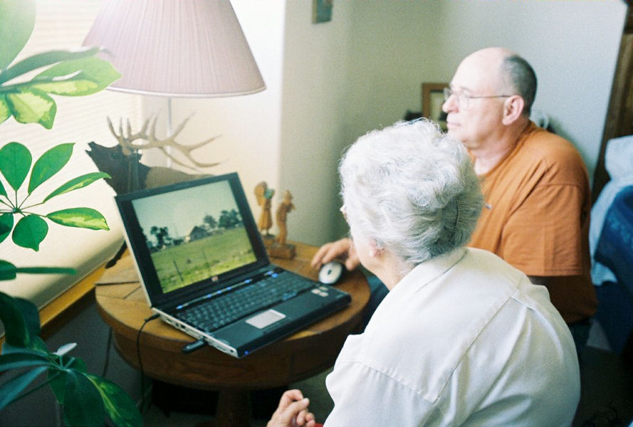 Ken shows Ophelia some pictures on his notebook computer